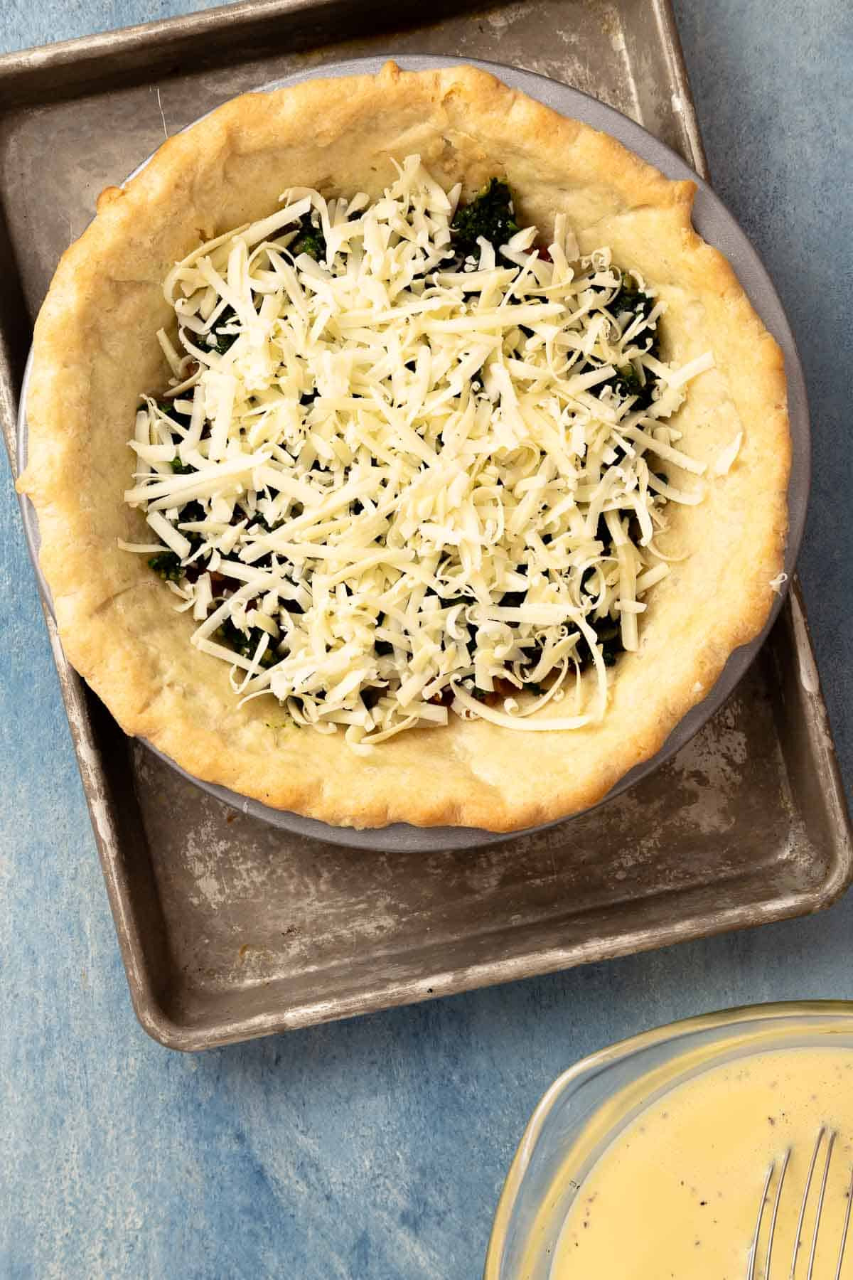 baked pie dough holding shredded cheese and spinach