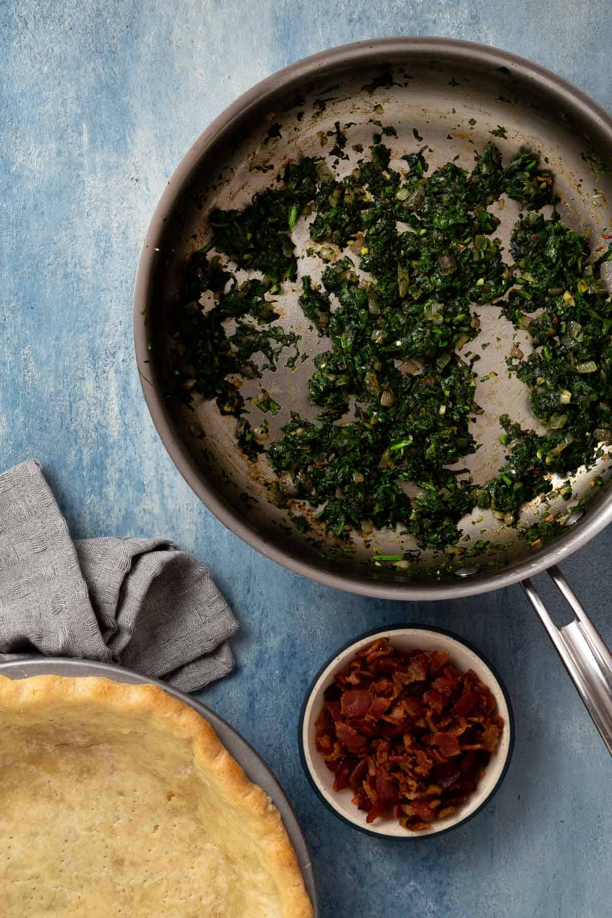 cooked spinach in a skillet next to a small bowl of cooked bacon