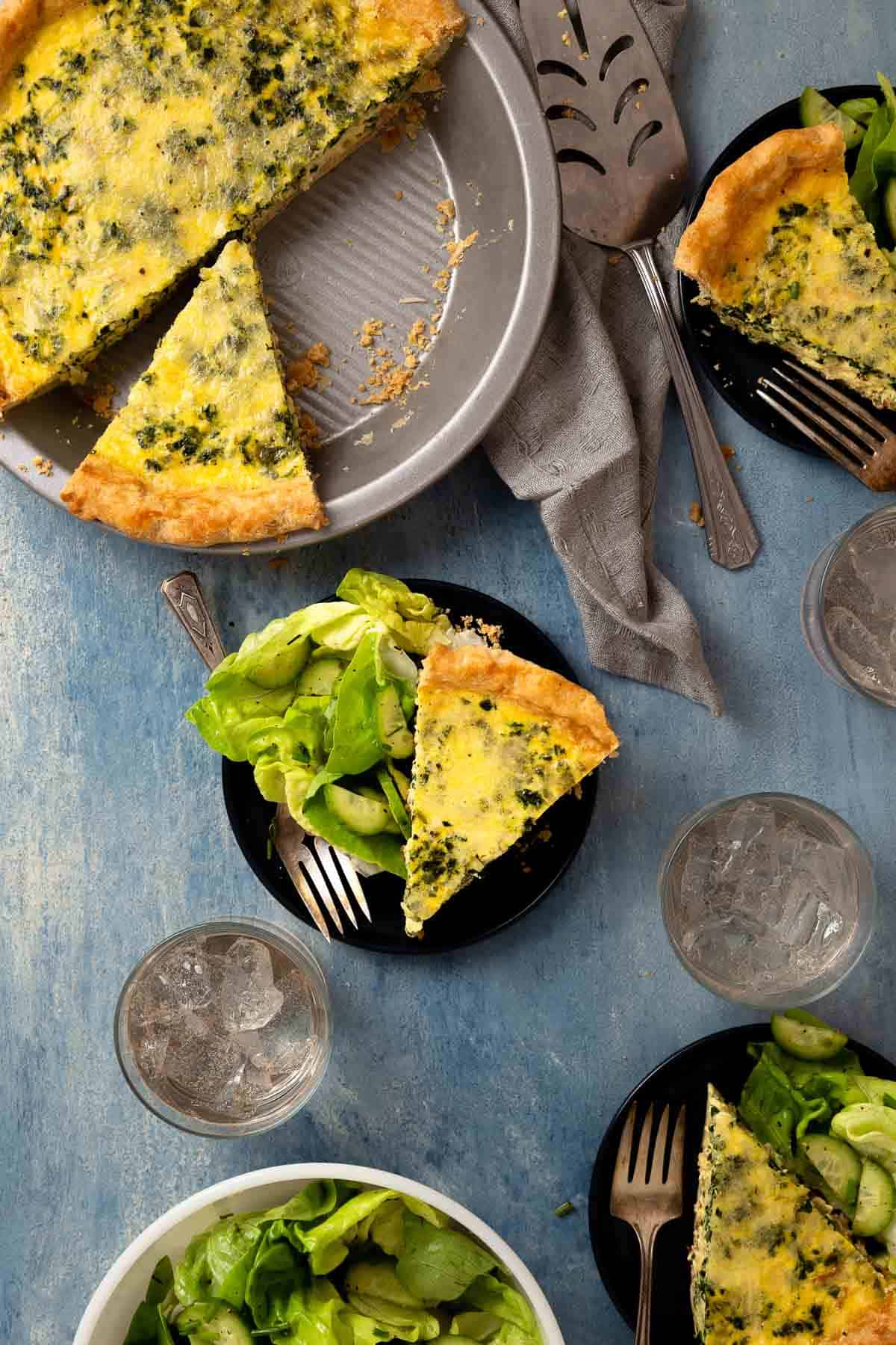 slices of yellow quiche on black plates with green salad on the side