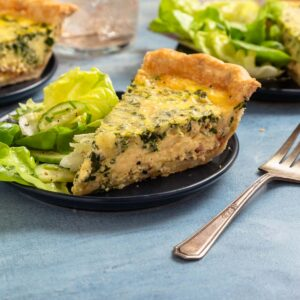 slice of quiche on a black plate next to green salad