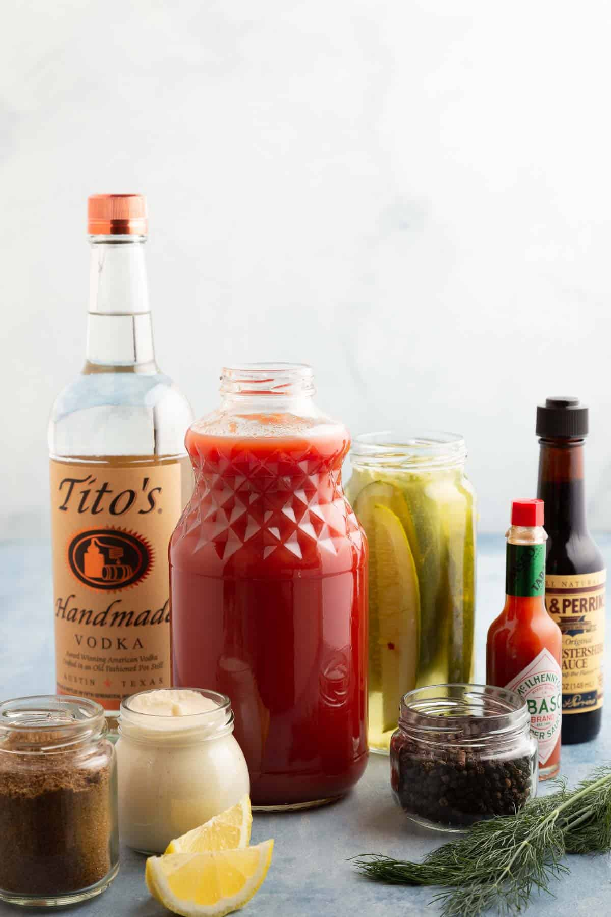 jars and bottles filled with the ingredients for a bloody mary