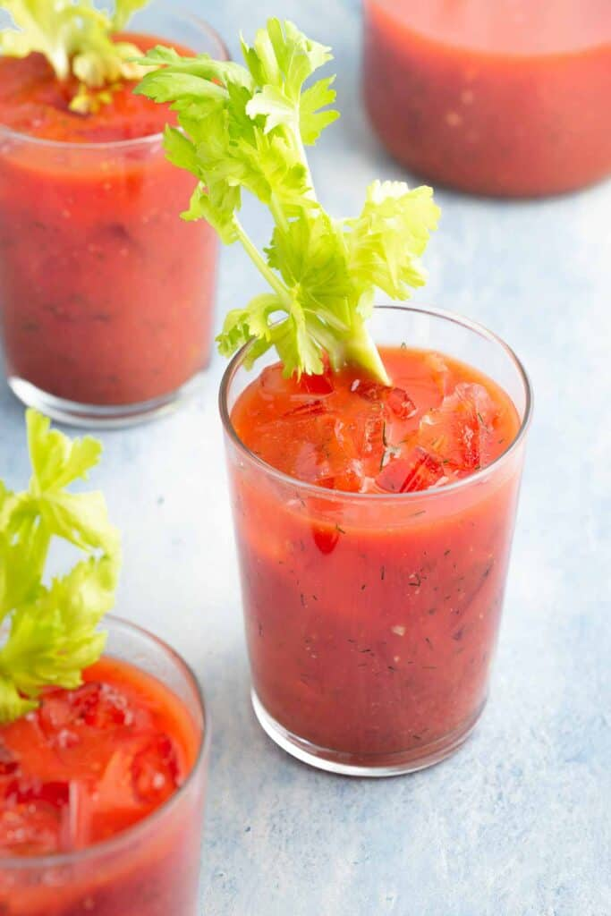 3 bloody mary's in glasses with celery stalks in each