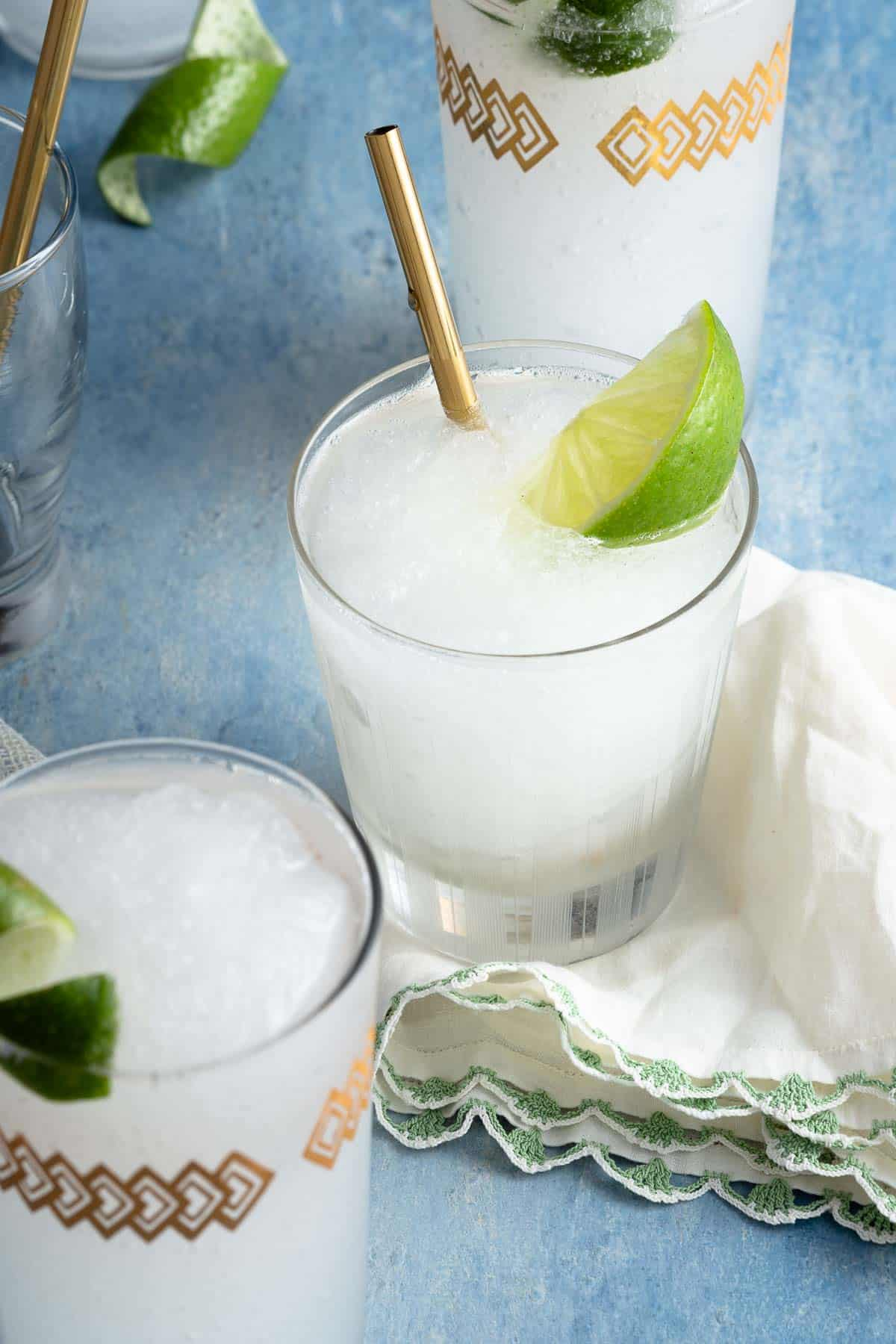 multiple glasses of white slushie drinks garnished with lime and gold straws