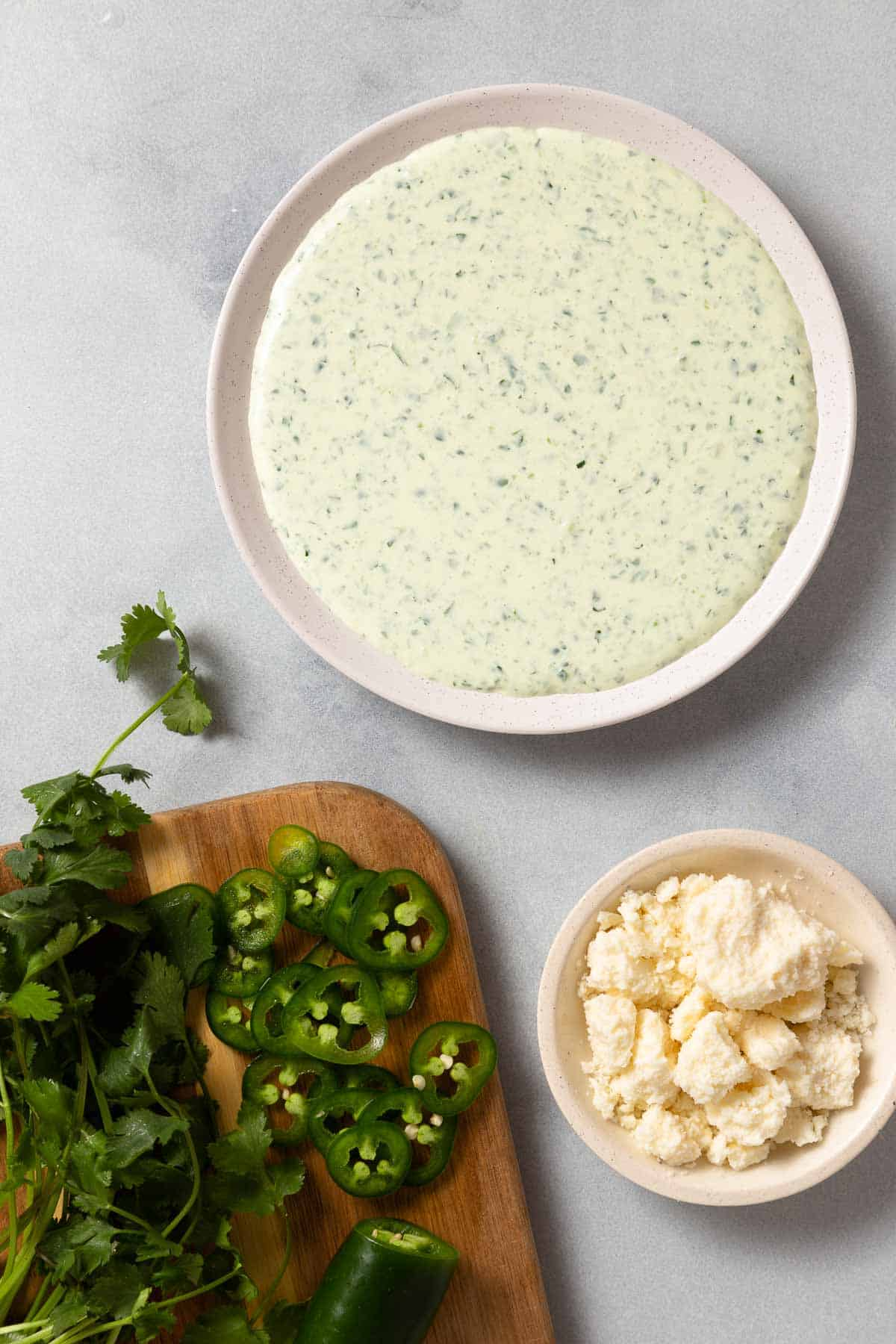 jalapeno dip in a white bowl next to chopped jalapenos, herbs, and cheese