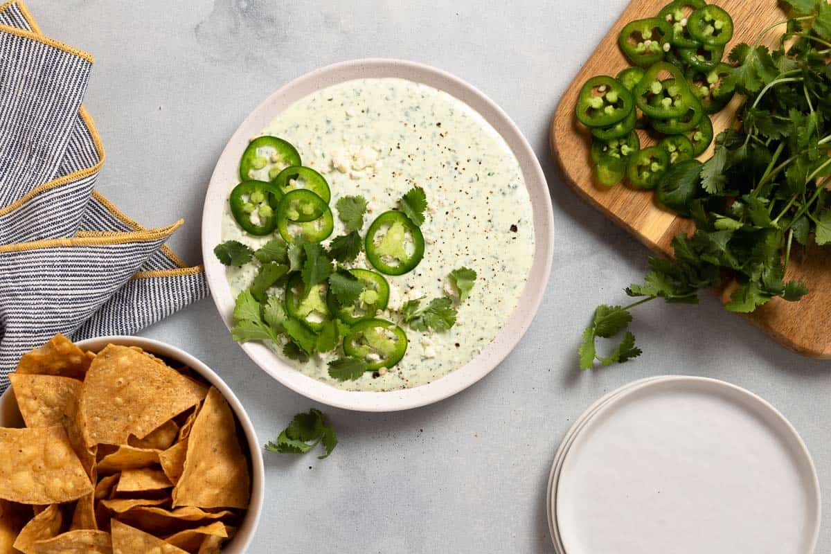 jalapeno dip in a white bowl next to tortilla chips and sliced jalapenos and herbs