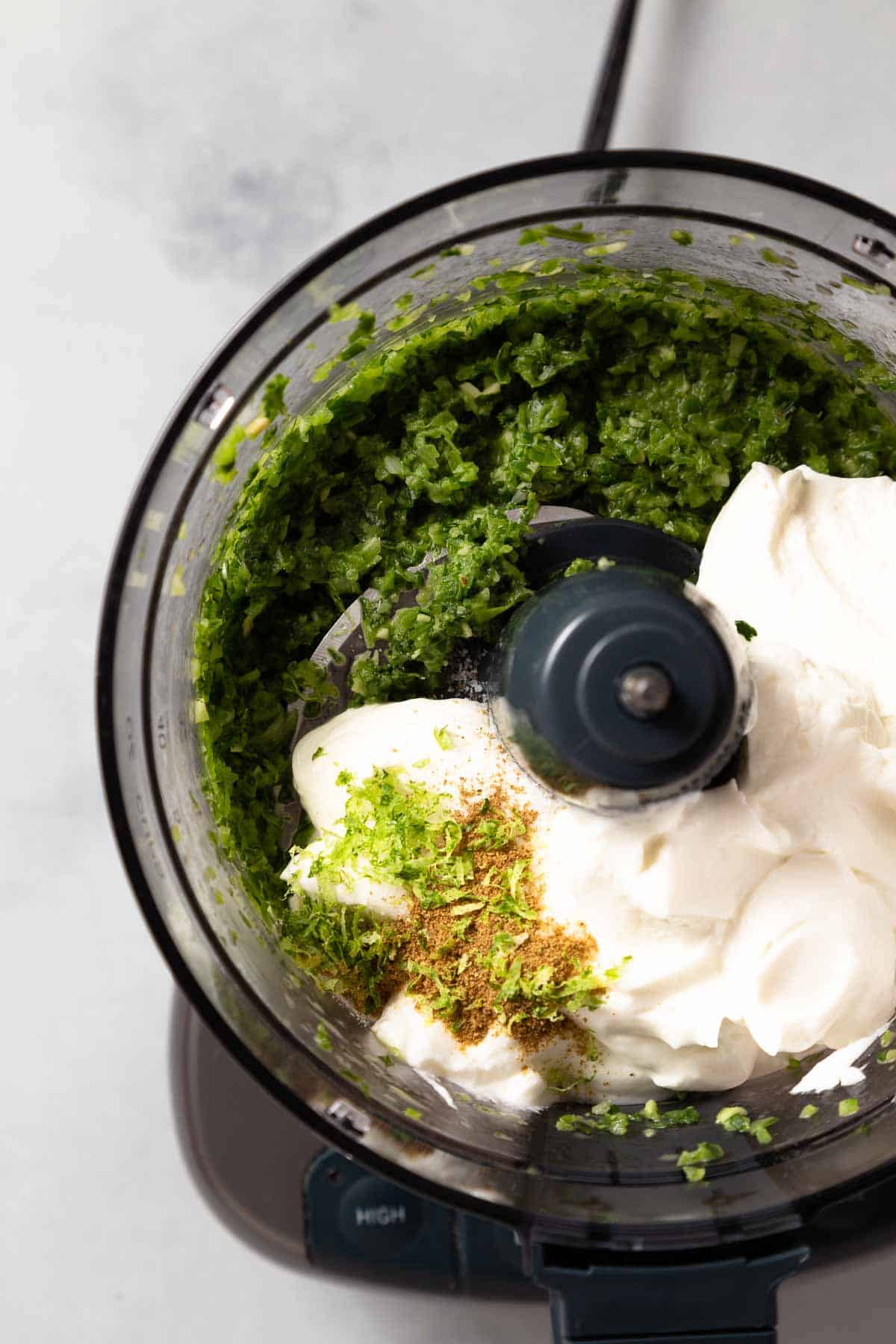 blended jalapenos and cilantro with seasonings and greek yogurt in a food processor