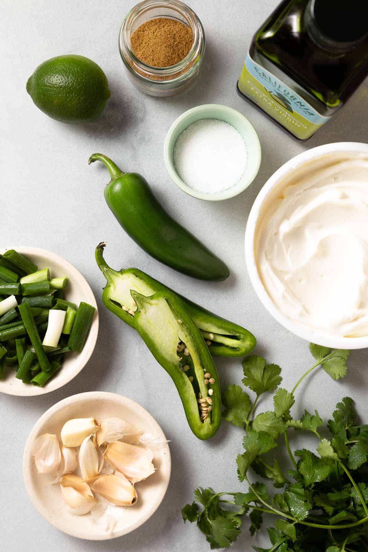 jalepeno peppers next to oil, greek yogurt, cilantro, and garlic