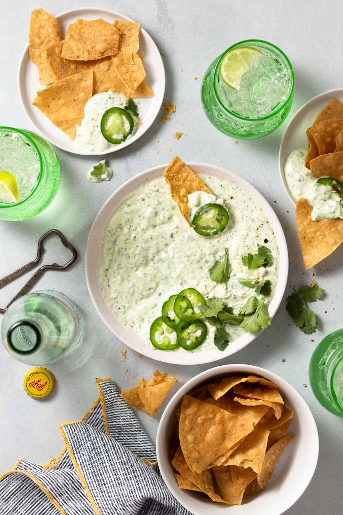 white jalapeno dip next to tortilla chips and cocktails