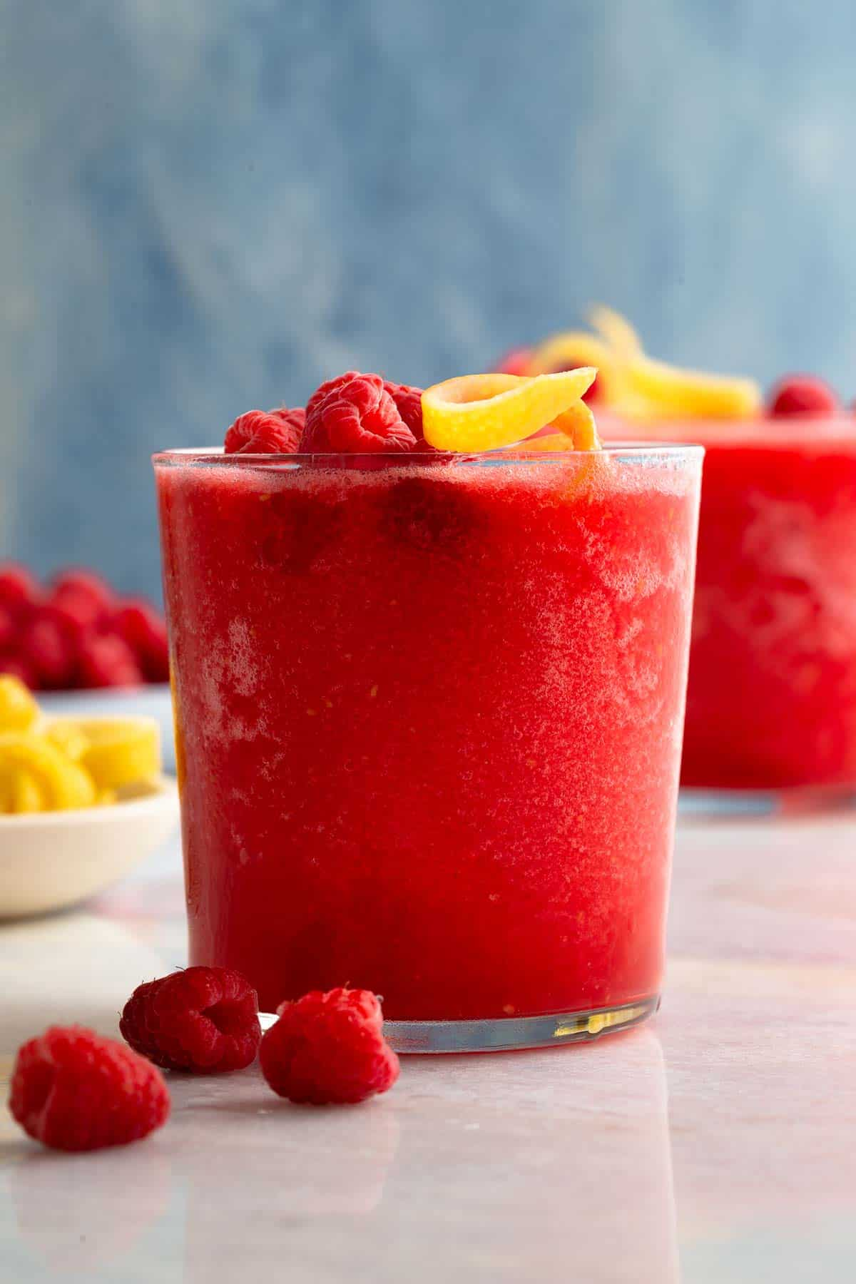 closeup on a red slushy cocktail in a glass garnished with raspberries and lemon peel