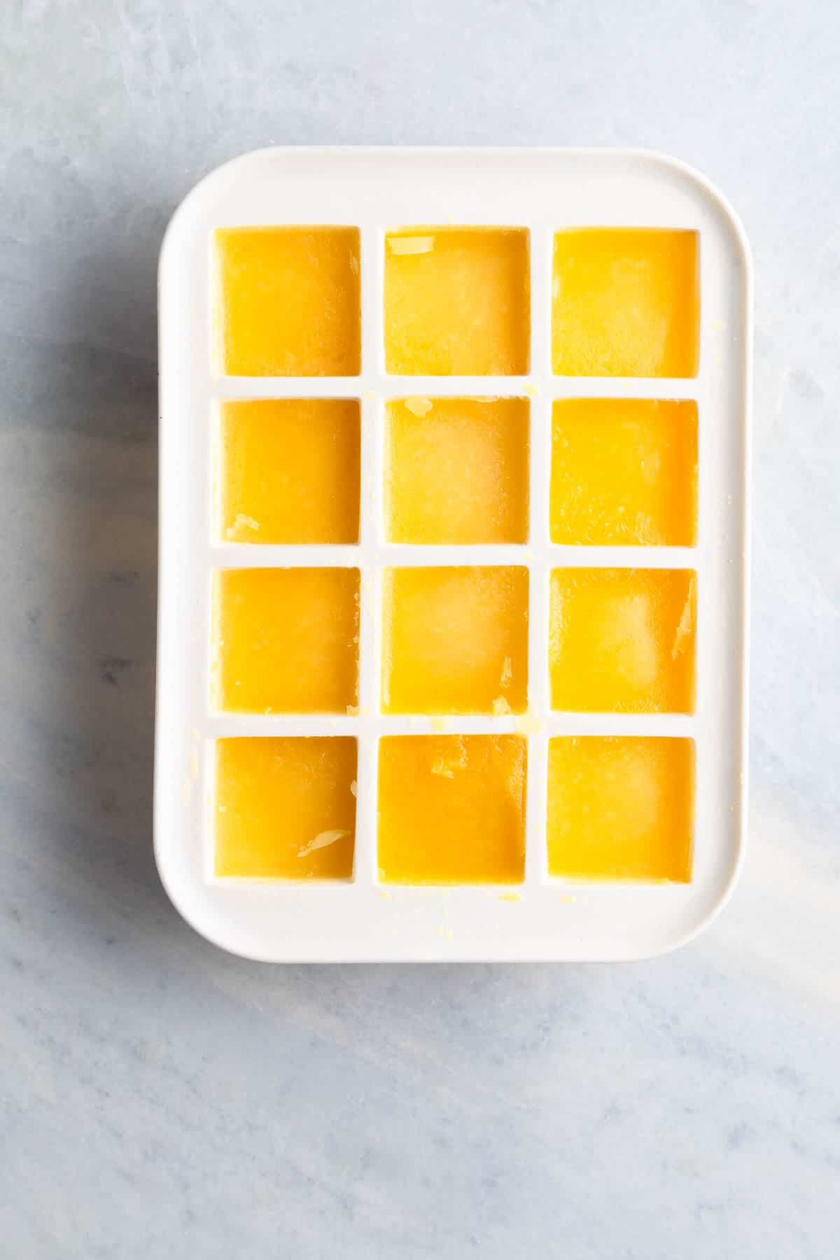 frozen orange juice in a white ice cube tray