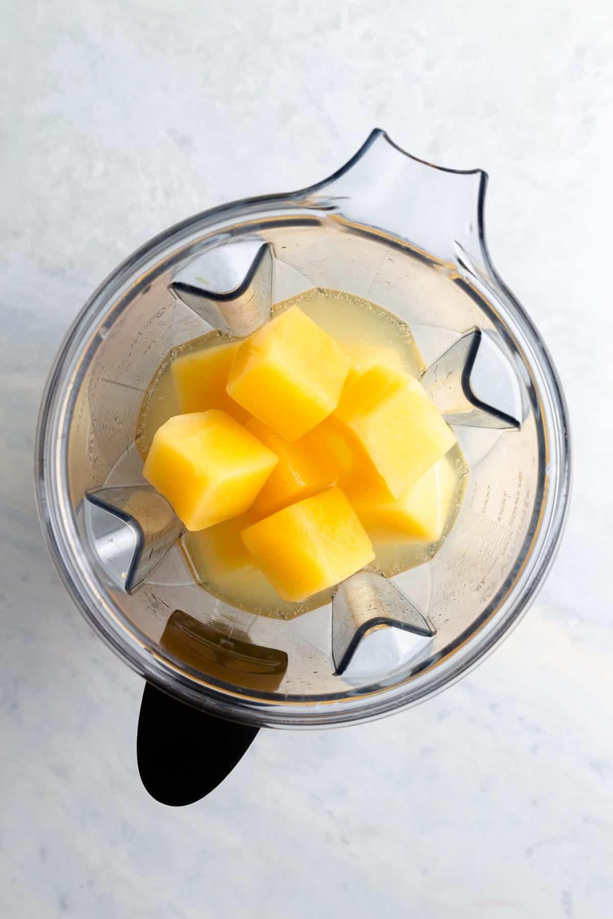 overhead view of orange juice cubes in a blender