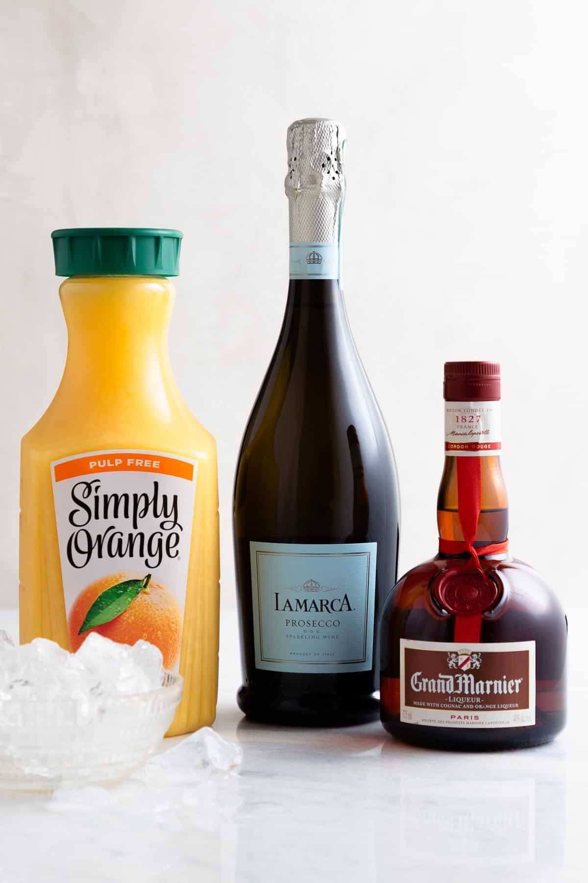 bottles of orange juice, prosecco, and grand marnier