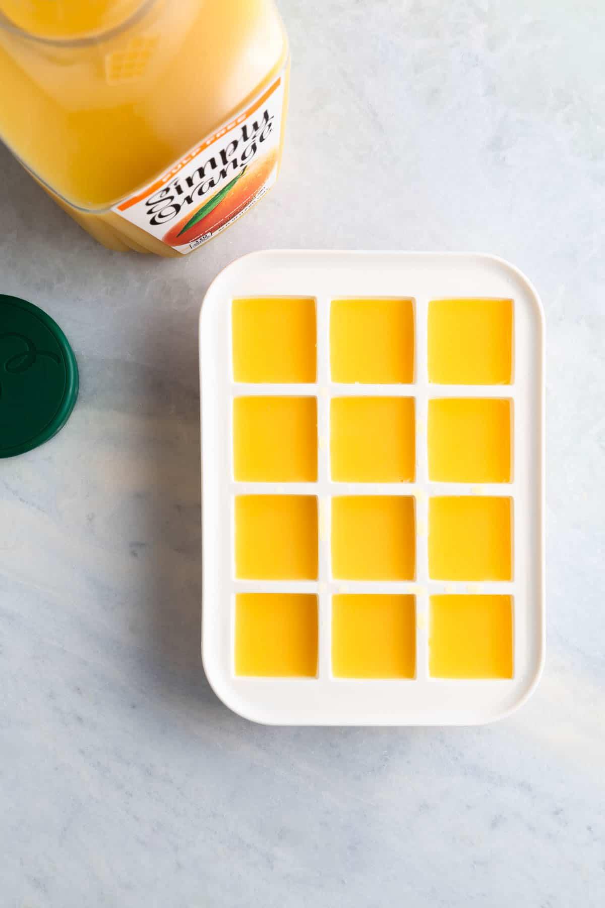 frozen orange juice in a white ice cube tray next to a bottle of orange juice