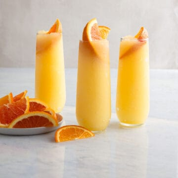 3 frozen mimosas garnished with orange slices next to a plate of slices oranges