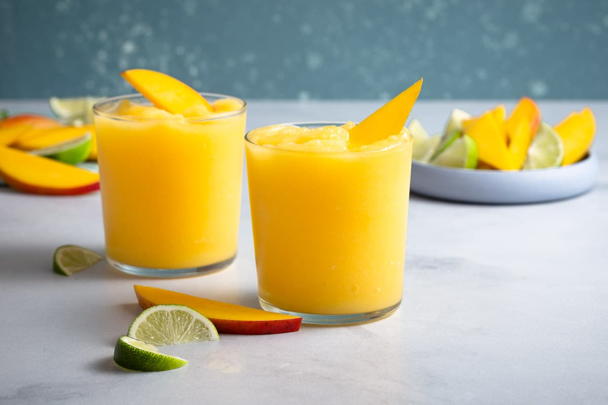 2 yellow mango margaritas and a plate of sliced fruit in the background