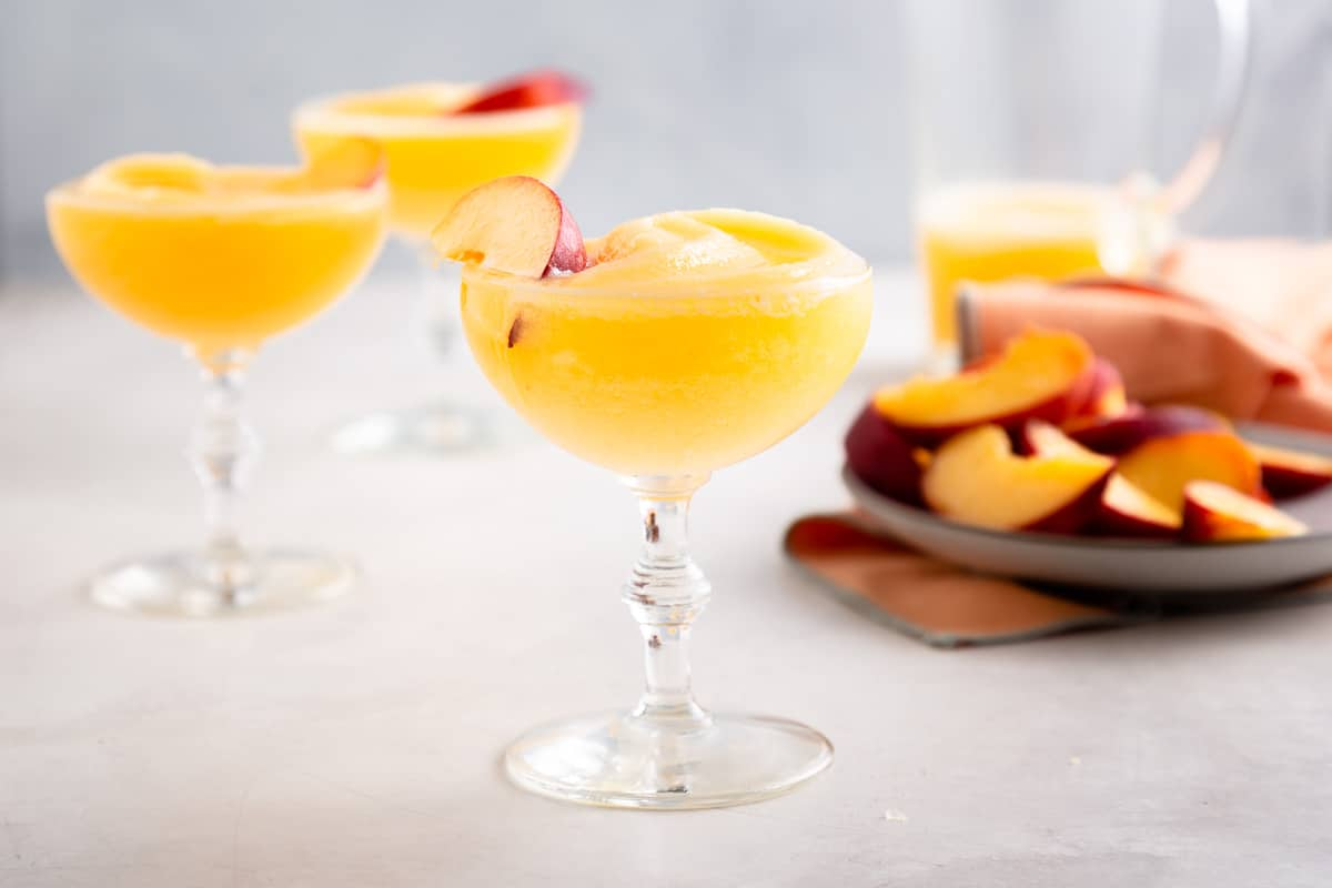3 glasses of slushy yellow drinks next to a plate of sliced peaches