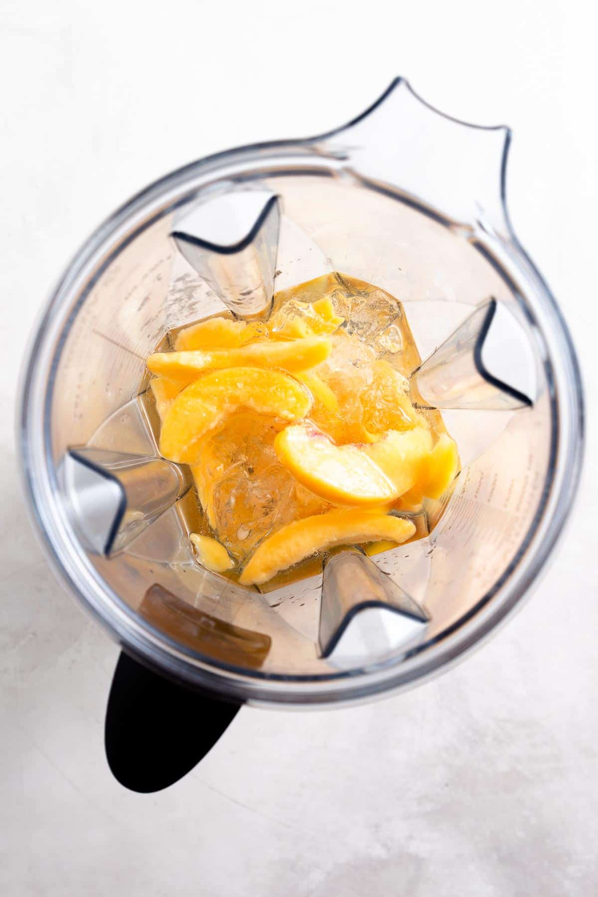 peaches, ice, and liquid in a large blender