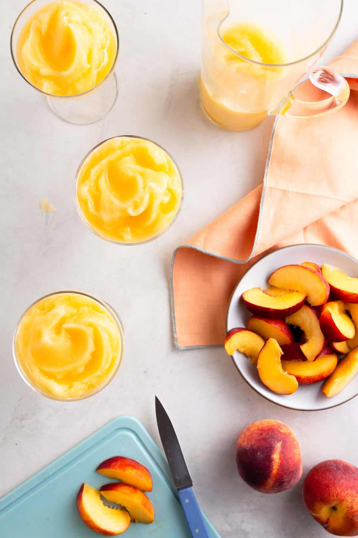 overhead view of 3 glasses filled with yellow slush next to a plate of sliced peaches