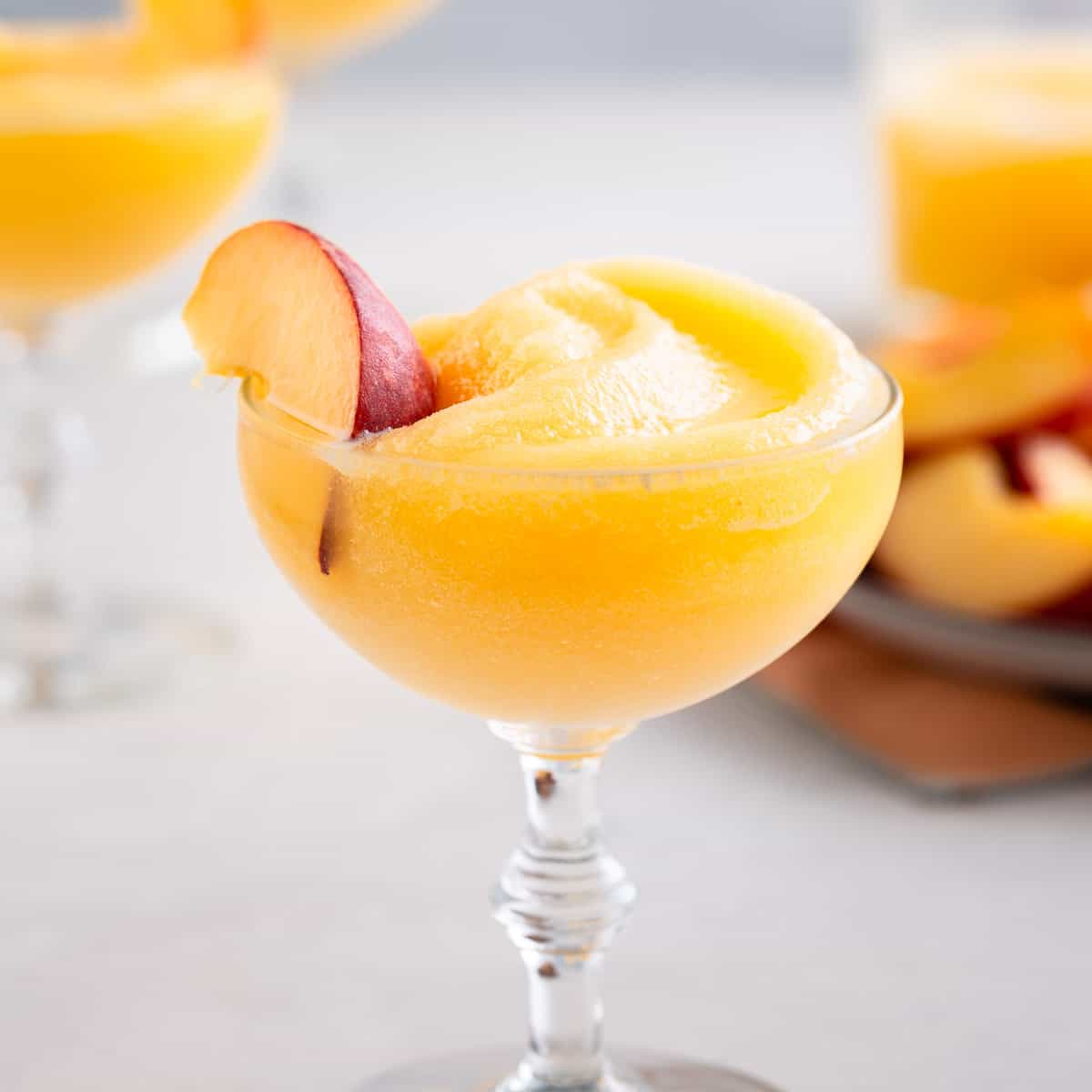 slushy yellow drink in a glass with a peach wedge