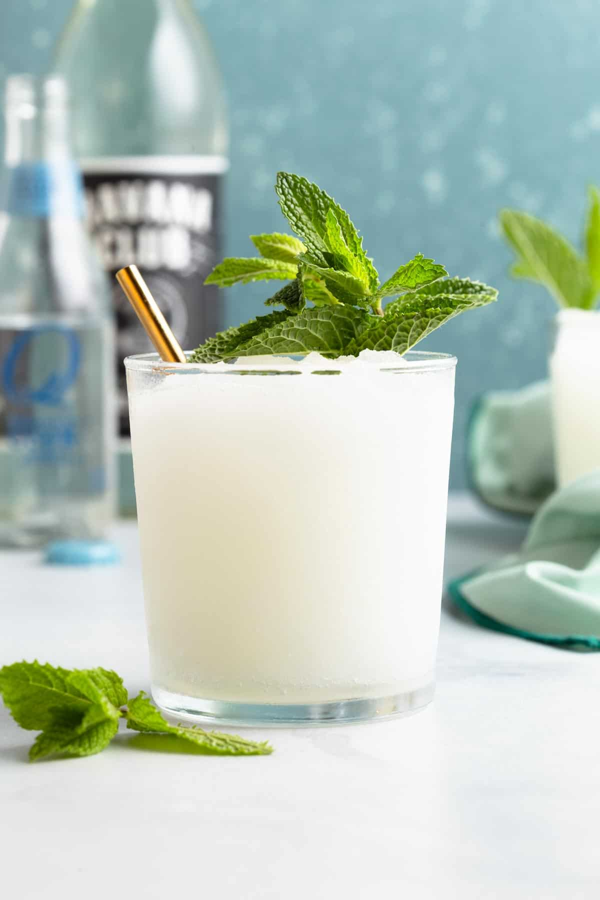 close up on a small glass holding a white frozen mojito topped with fresh mint