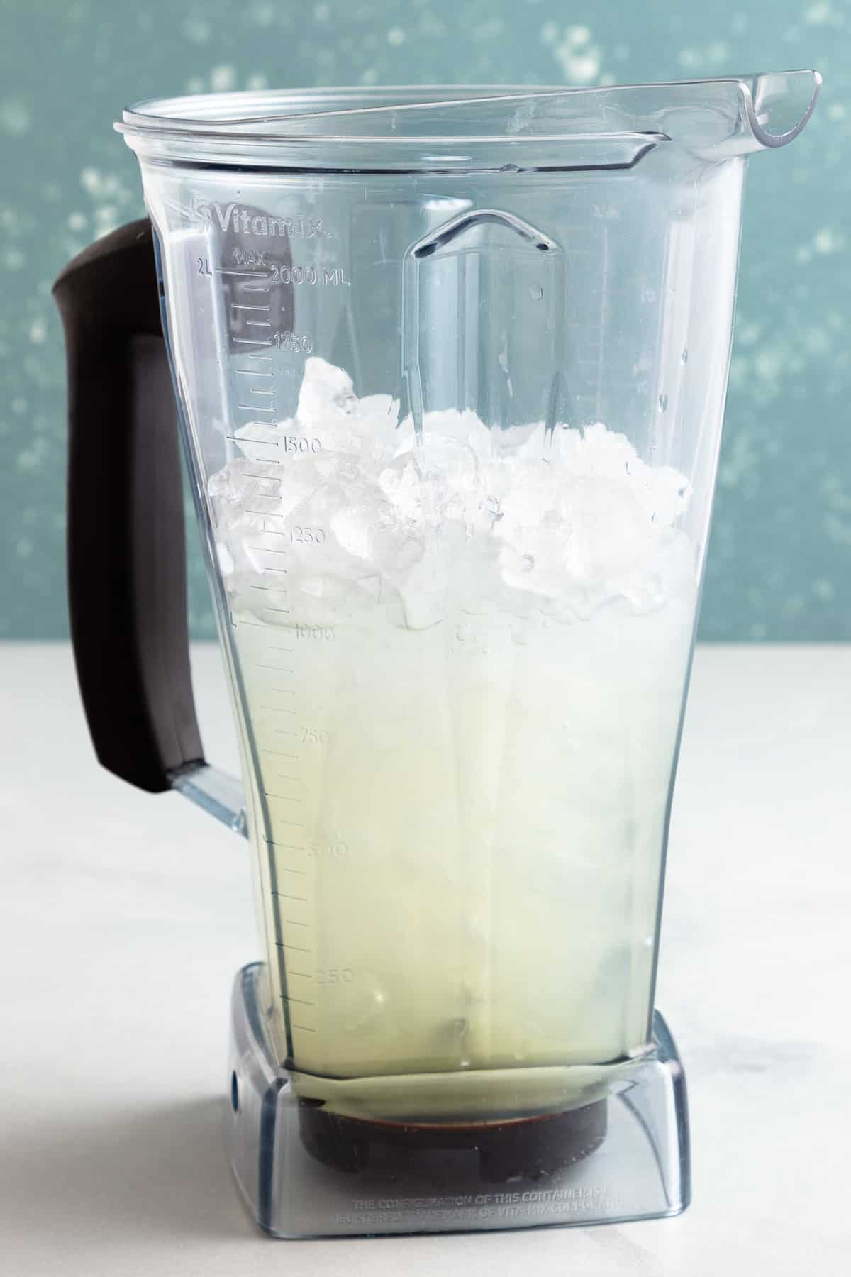large blender filled with ice and clear liquid