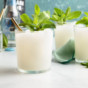 glasses holding a white slushy cocktail and topped with mint leaves