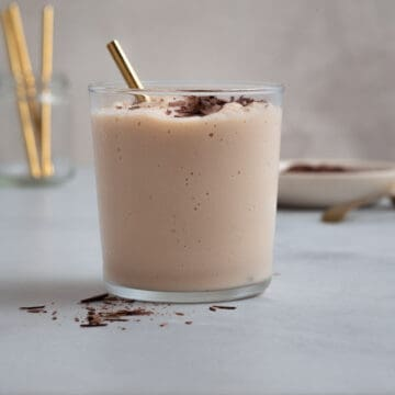 small glass filled with a blended chocolate cocktail topped with chocolate shavings