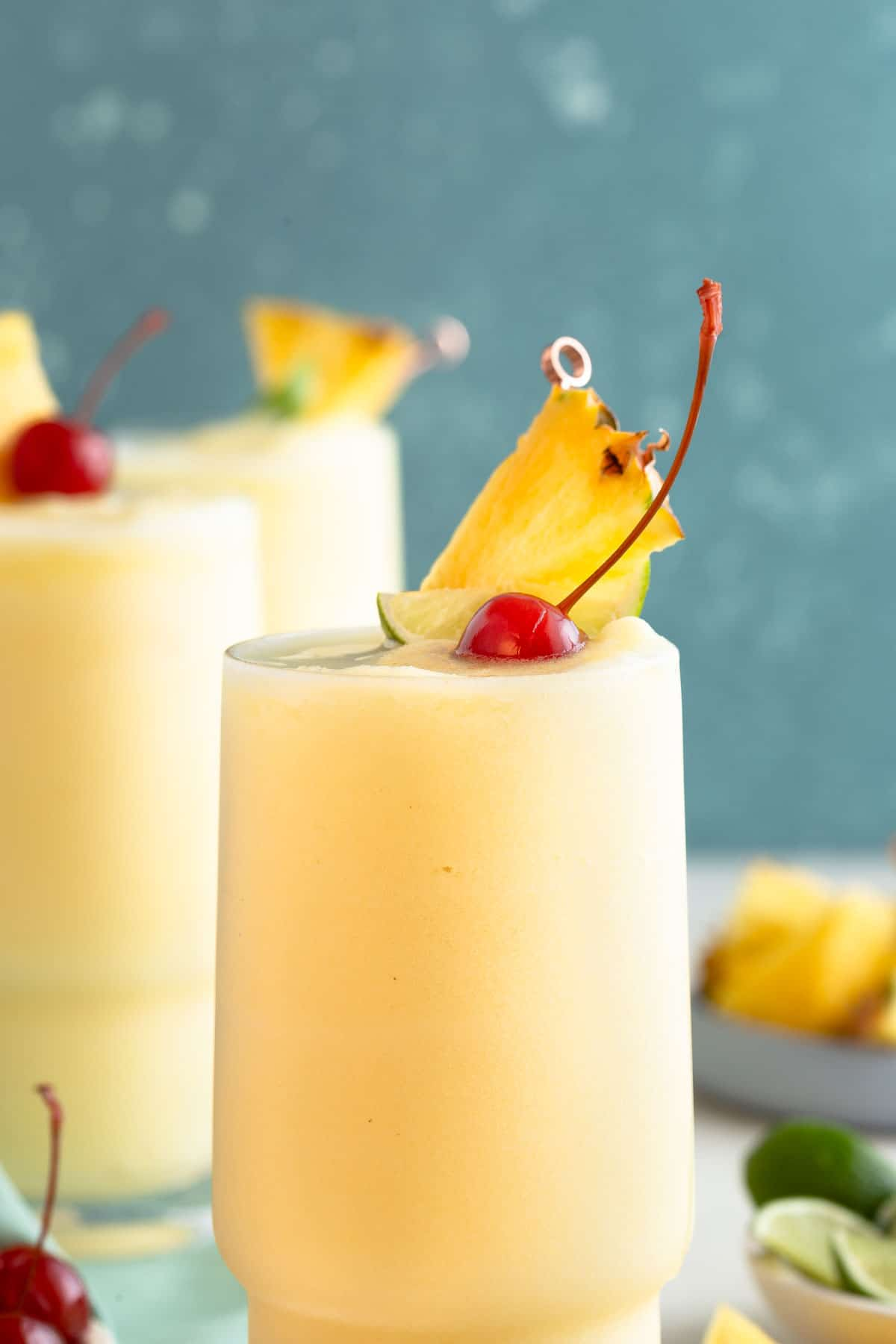 close up on a yellow slushy drink topped with pineapple, lime, and cherry
