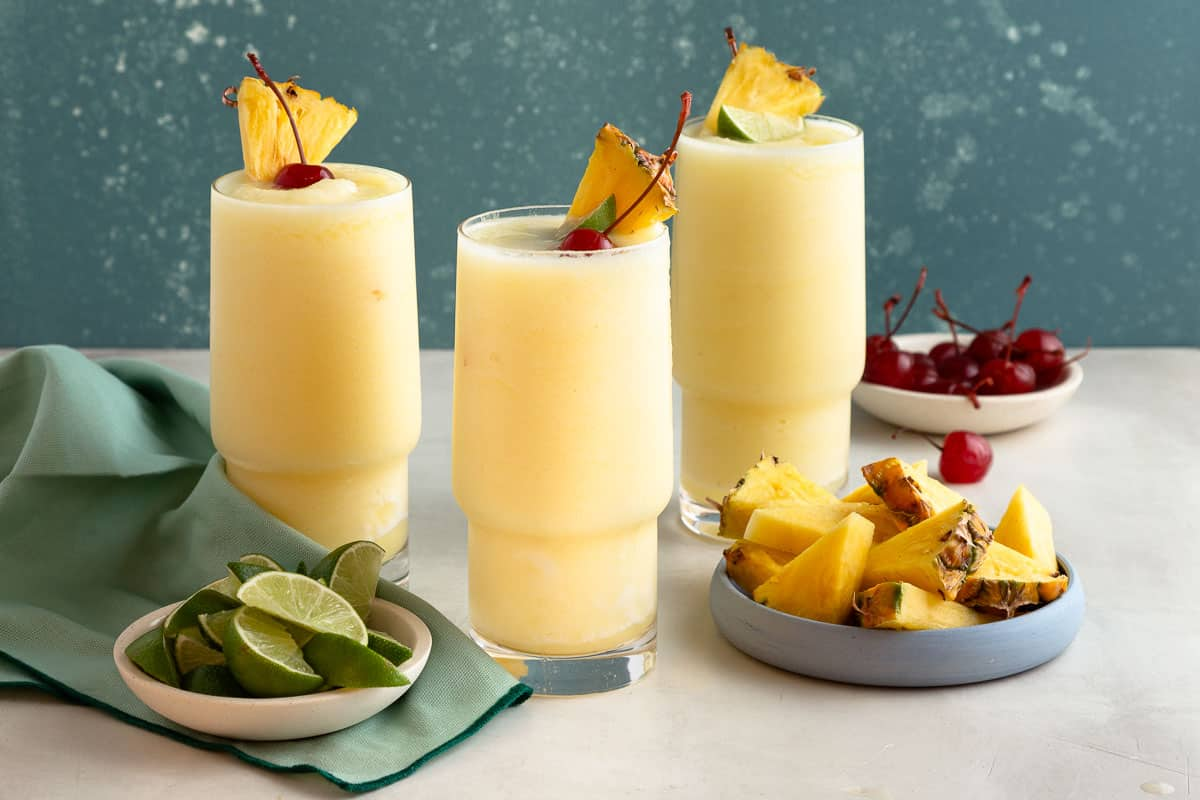 3 slushy yellow drinks in tall glasses next to plates on pineapple, lime, and cherries