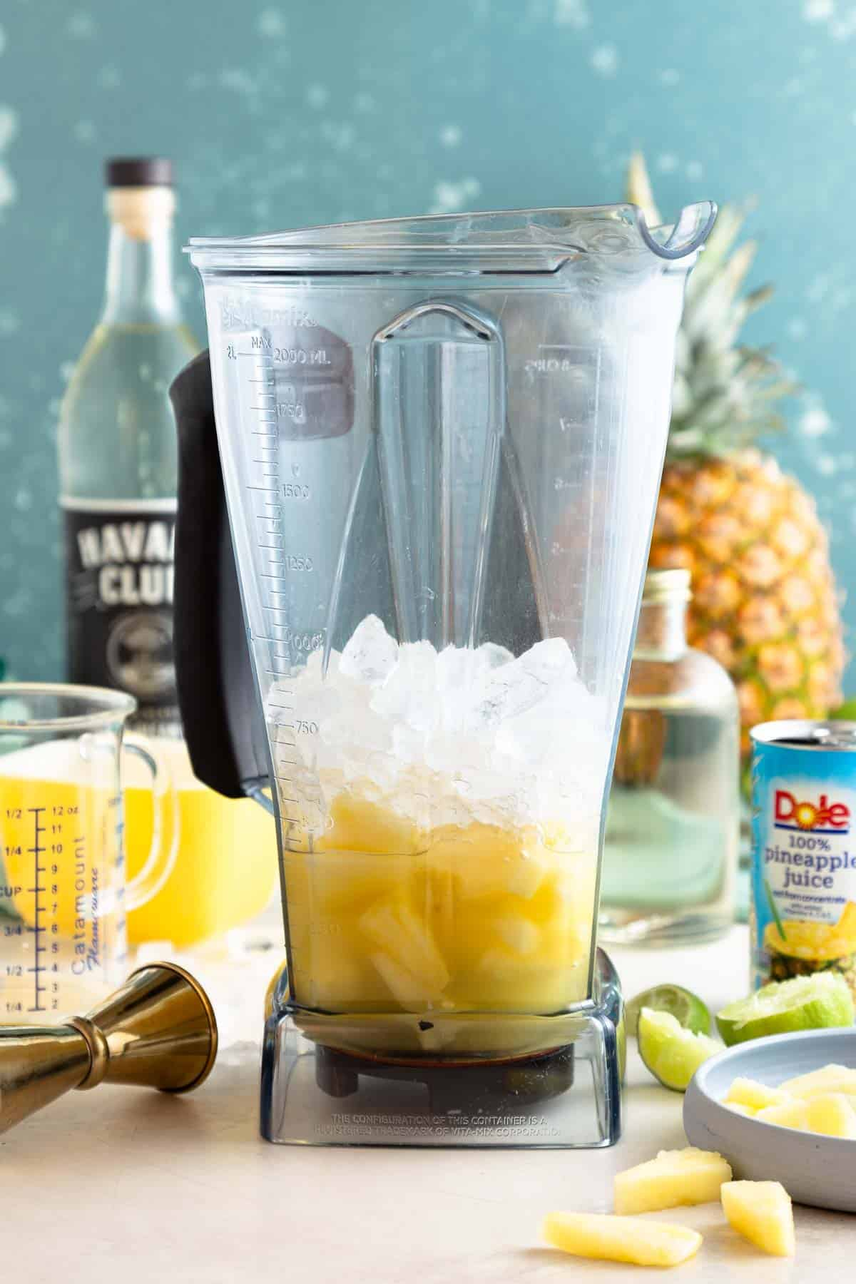 ice, pineapple, and liquid in a large blender bowl