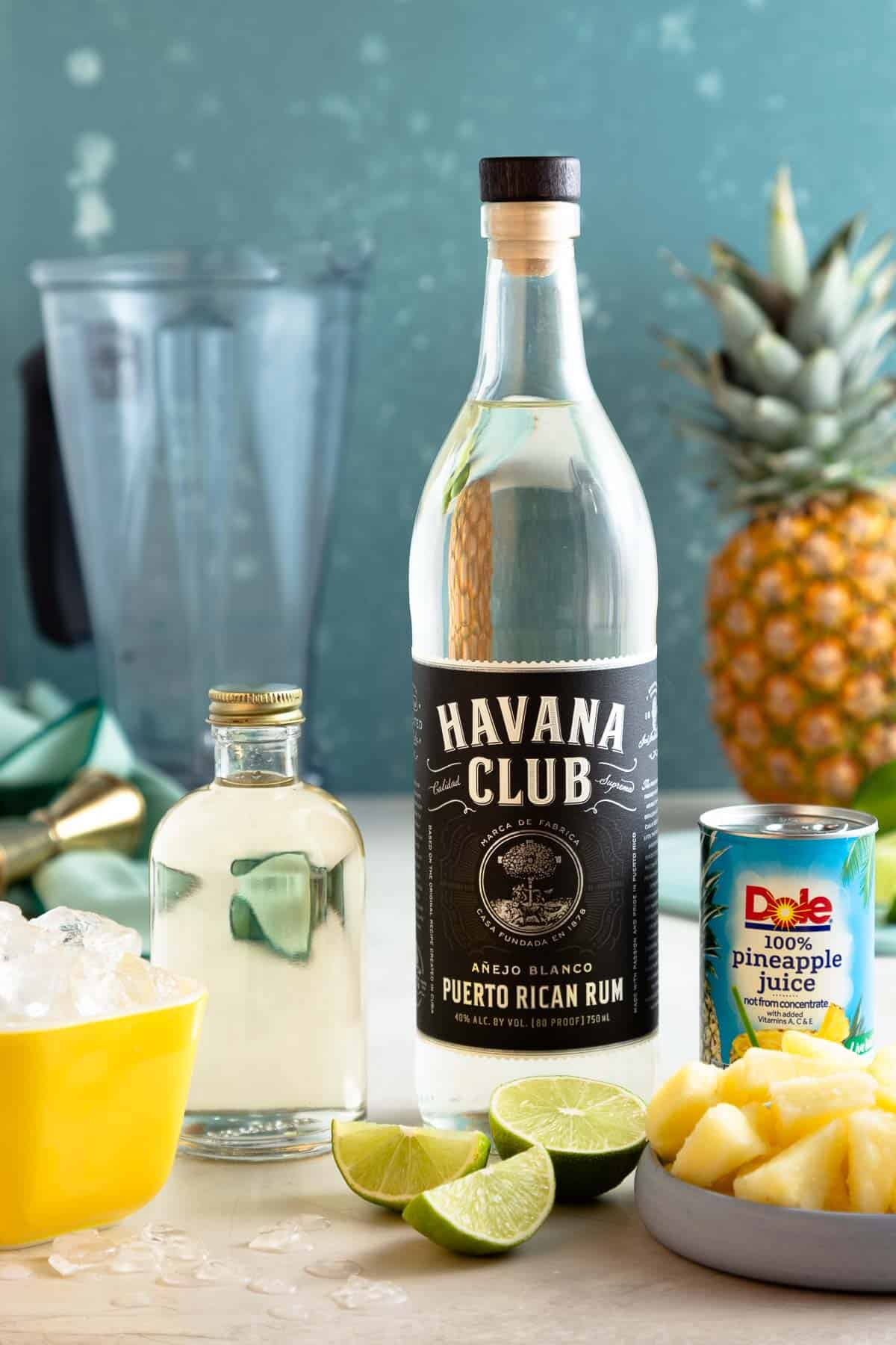 bottles of rum, syrup, and pineapple juice next to pineapple chunks and lime