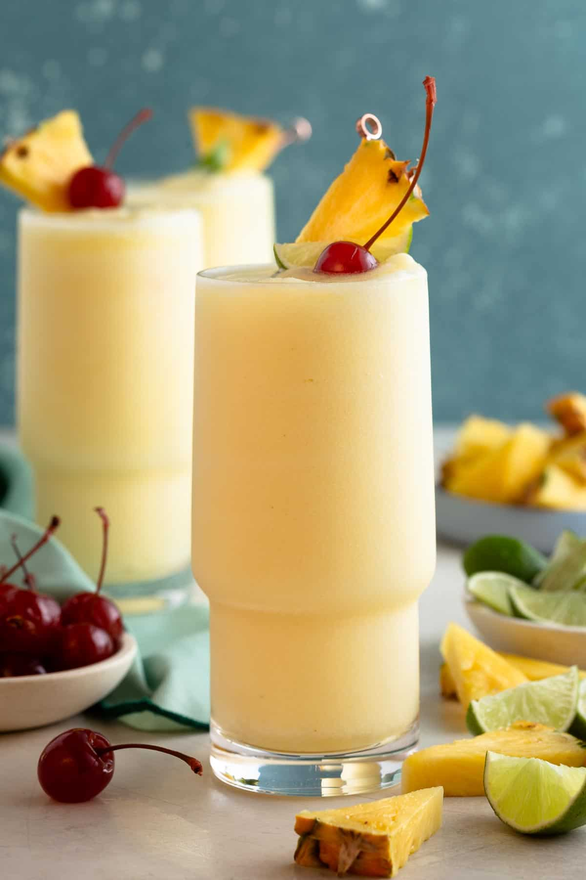 yellow slushy drink in a tall glass topped with pineapple, lime, and cherry