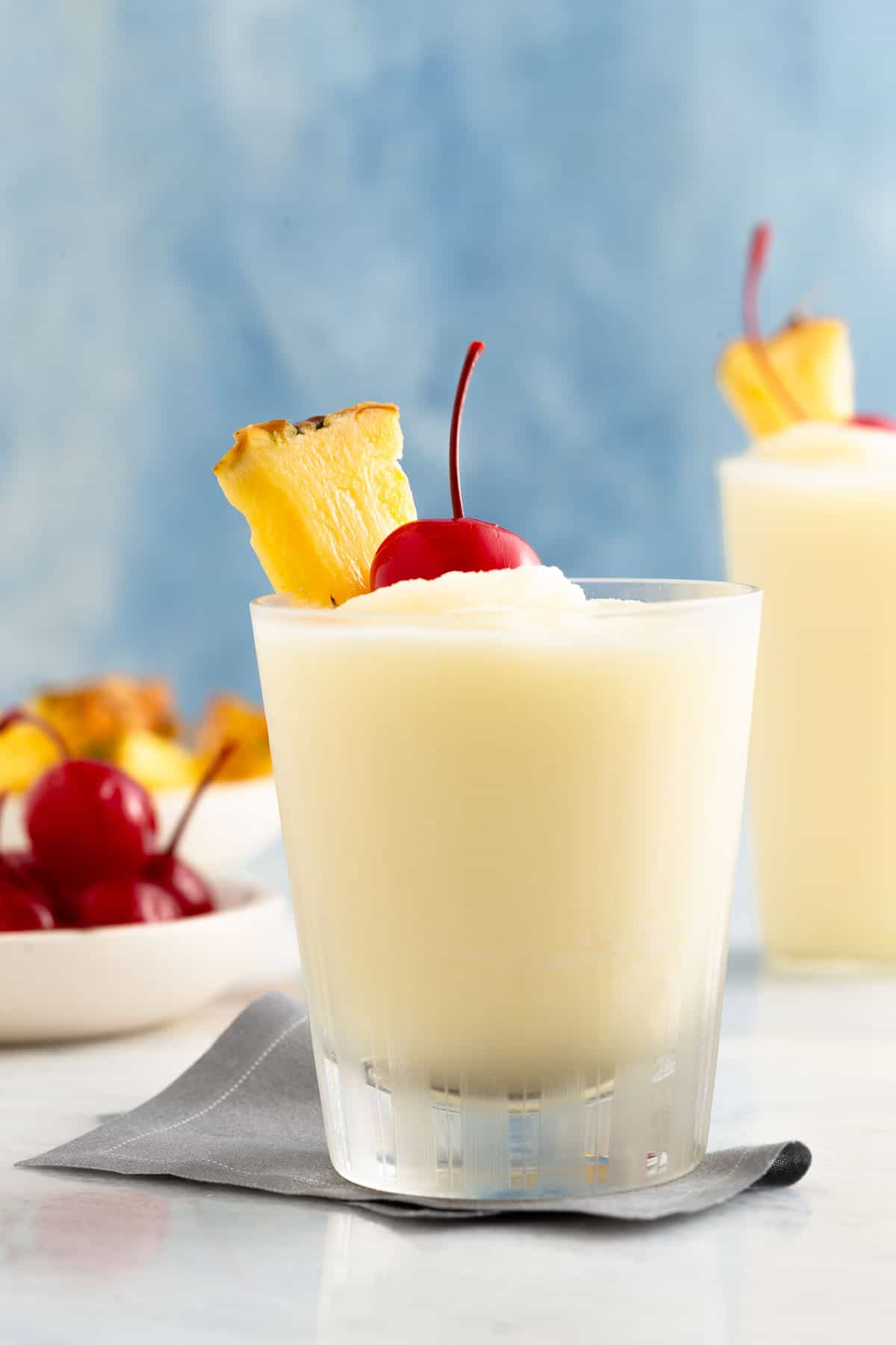 close up on a white frozen cocktail topped with a cherry and pineapple