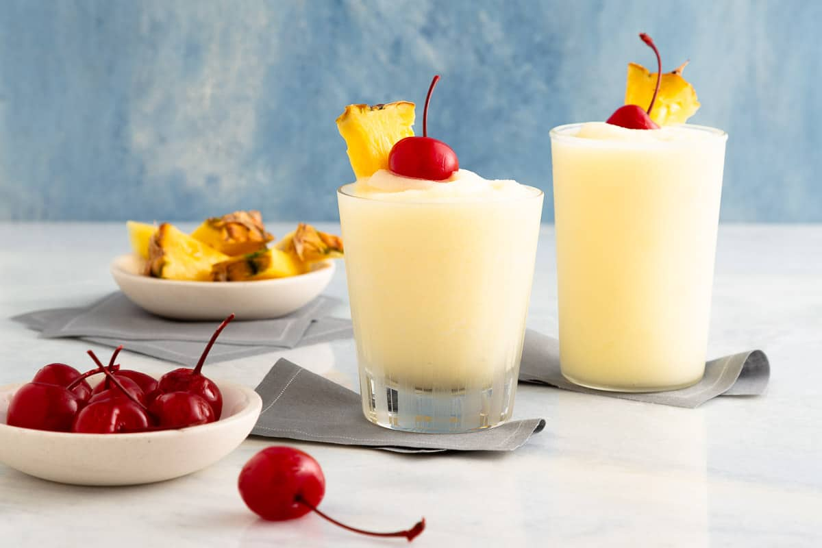 2 white slushy cocktails next to plates with cherries and pineapple
