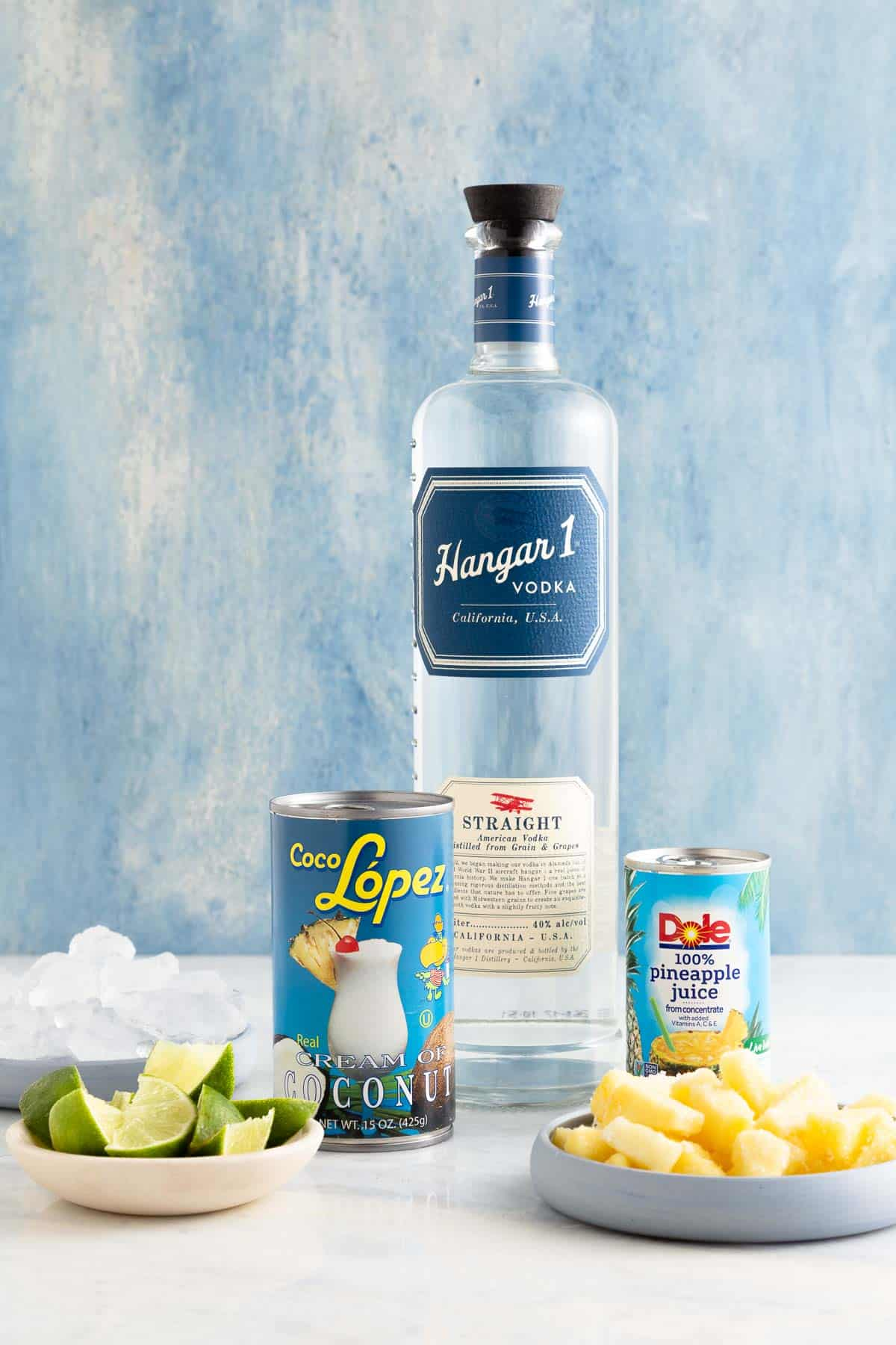 bottle of vodka next to cans of coconut, pineapple juice, and white plates with pineapple and lime