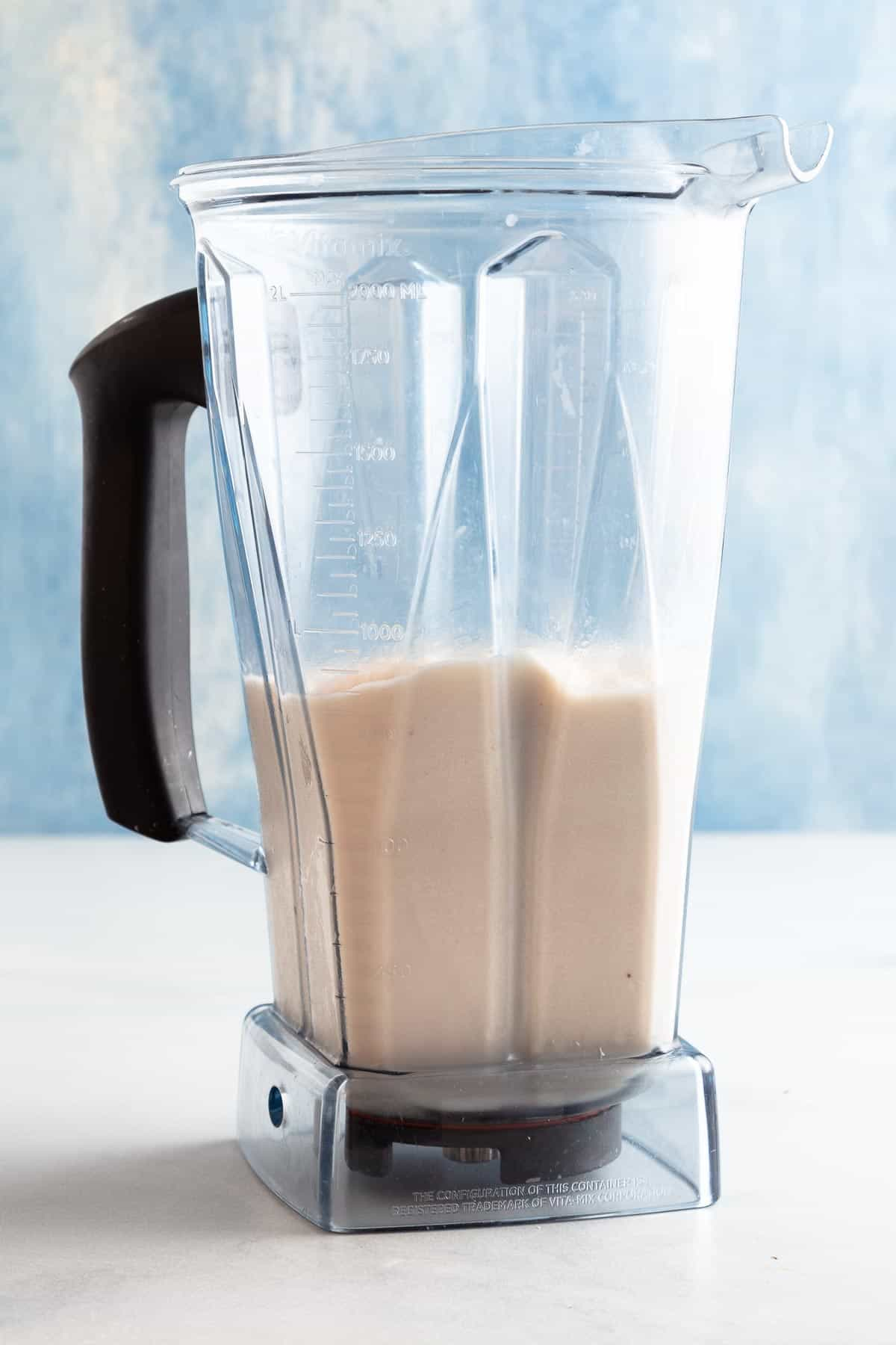 vitamix blender with blended light brown cocktail in front of blue background