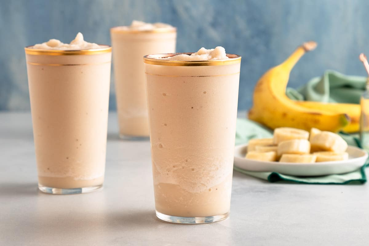 horizontal image of three light brown frozen cocktails with sliced and whole bananas in the background