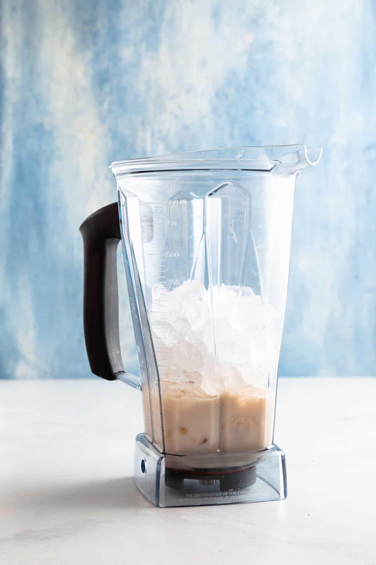 vitamix blender filled with drink ingredients in front of a blue background