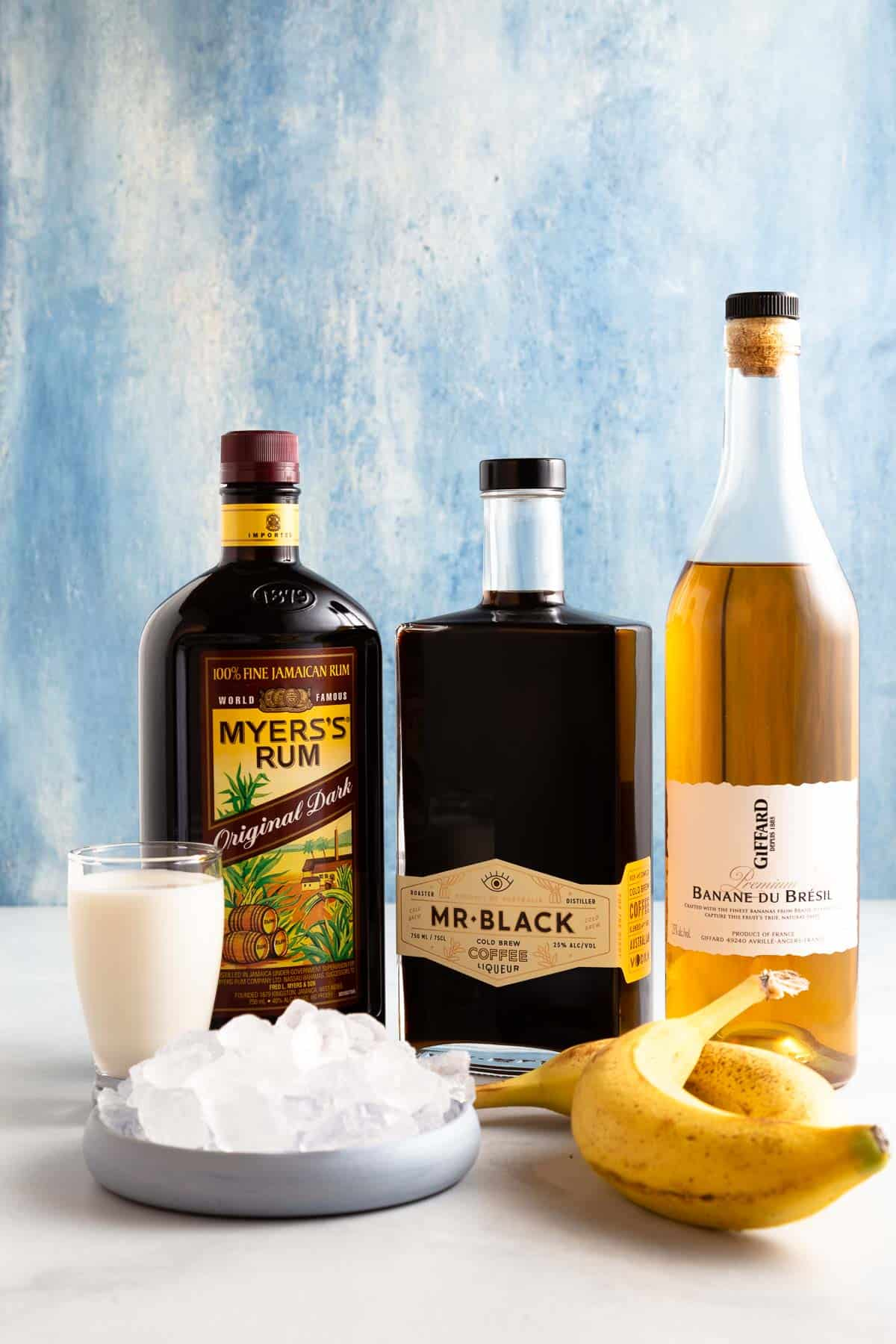 Straight on image of a bottle of Myer's Dark Run, Mr. Black coffee liqueur, and Giffard banana liqueur wiith a small glass of milk, a bowl of ice and two bananas