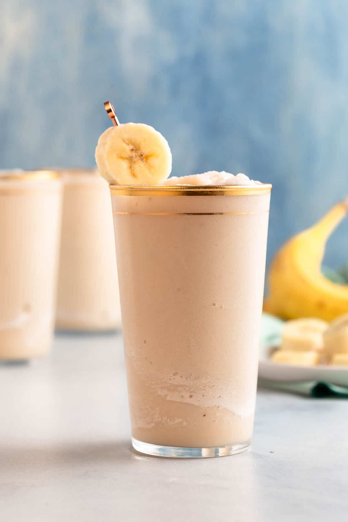 frozen blended cocktail in a gold rimmed glass with a banana garnish