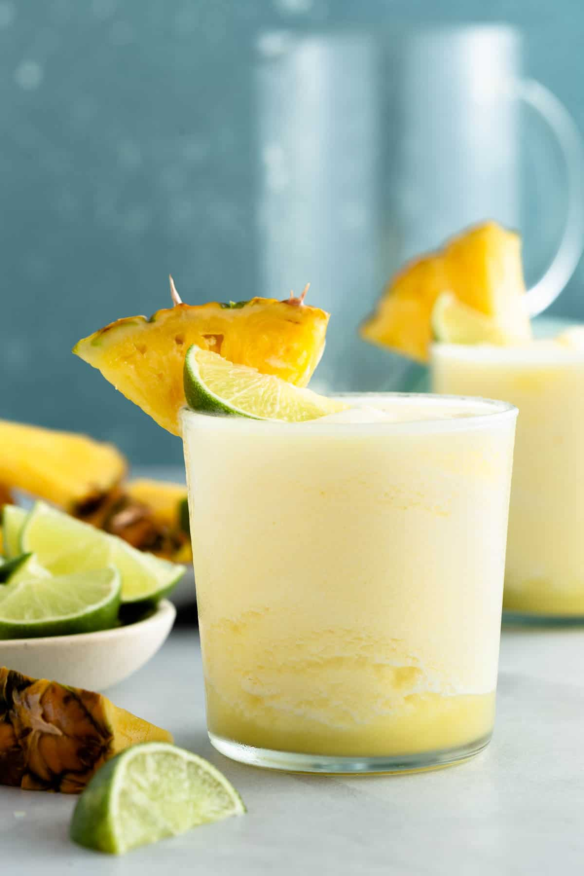 close up on a yellow frozen cocktail topped with lime and pineapple