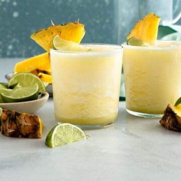2 yellow frozen drinks next to small bowls of lime wedges and pineapple