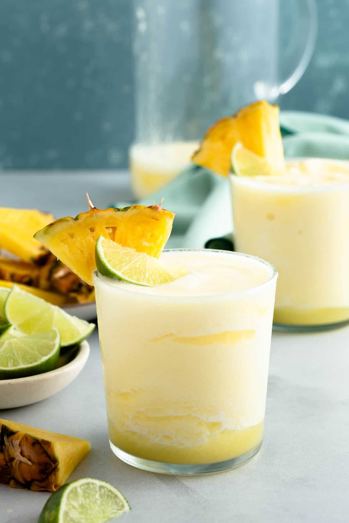 2 yellow frozen drinks topped with lime and pineapple