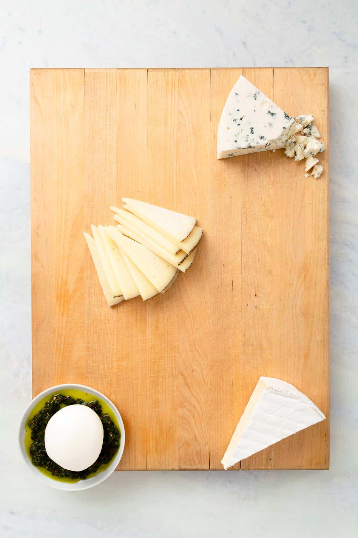 putting white cheeses on a large wood board