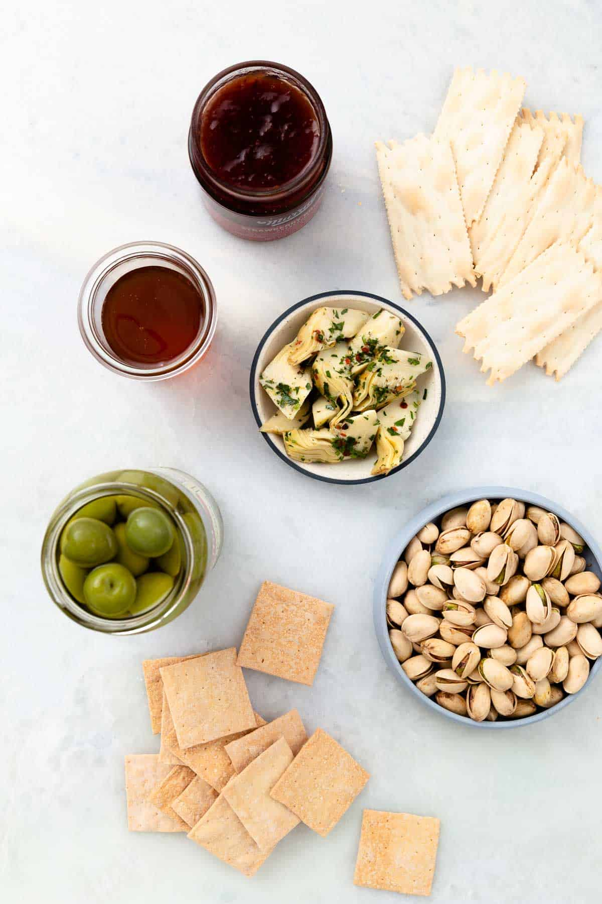 small bowls and jars filled with nuts, green olives, and jam with crackers on the side