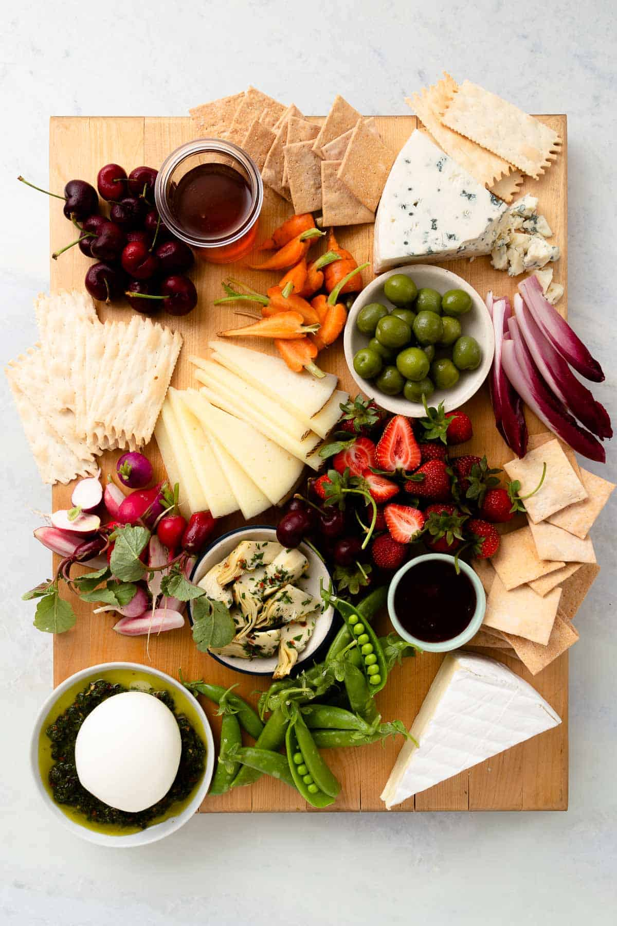 filling a large wood board with vegetables, crackers, green olives, jam, and white cheeses