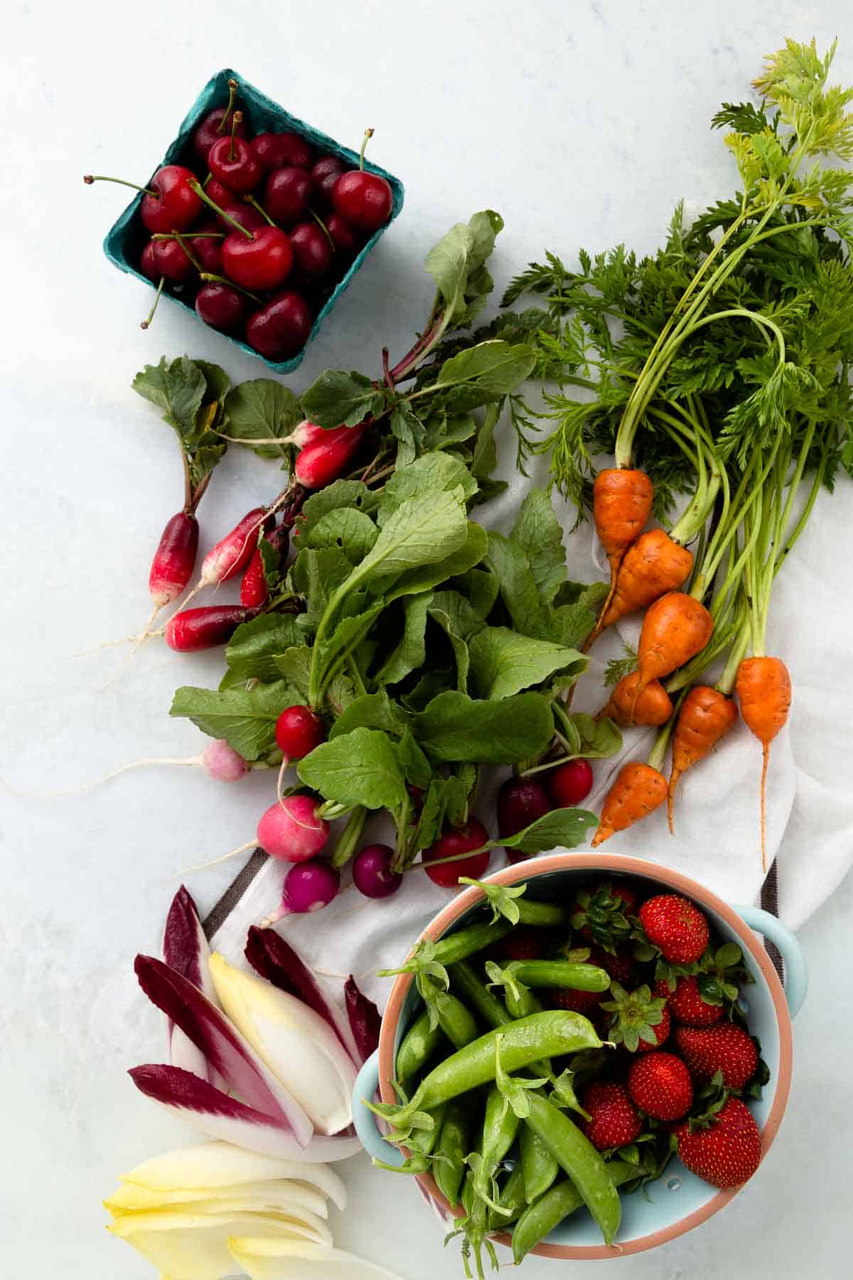 fresh green and red vegetables in small bowls on a white back drop