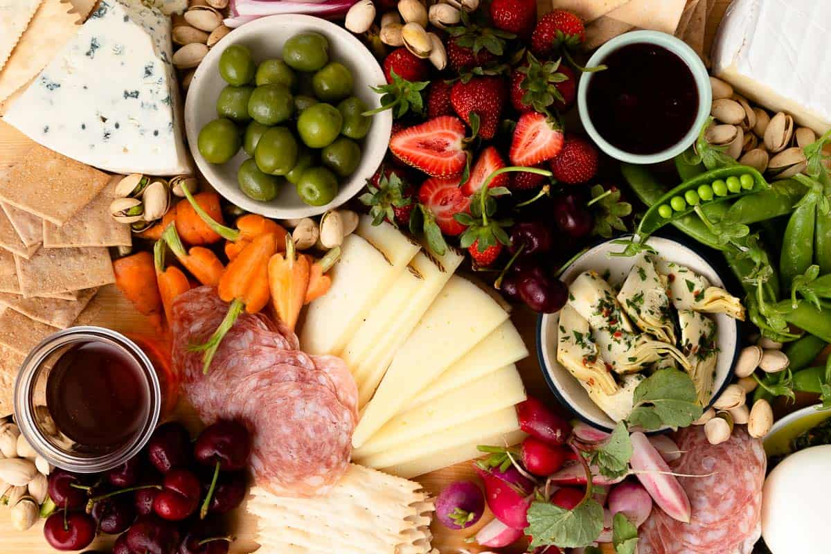 close up on a packed snack board with cheese, meat, fruit, and vegetables