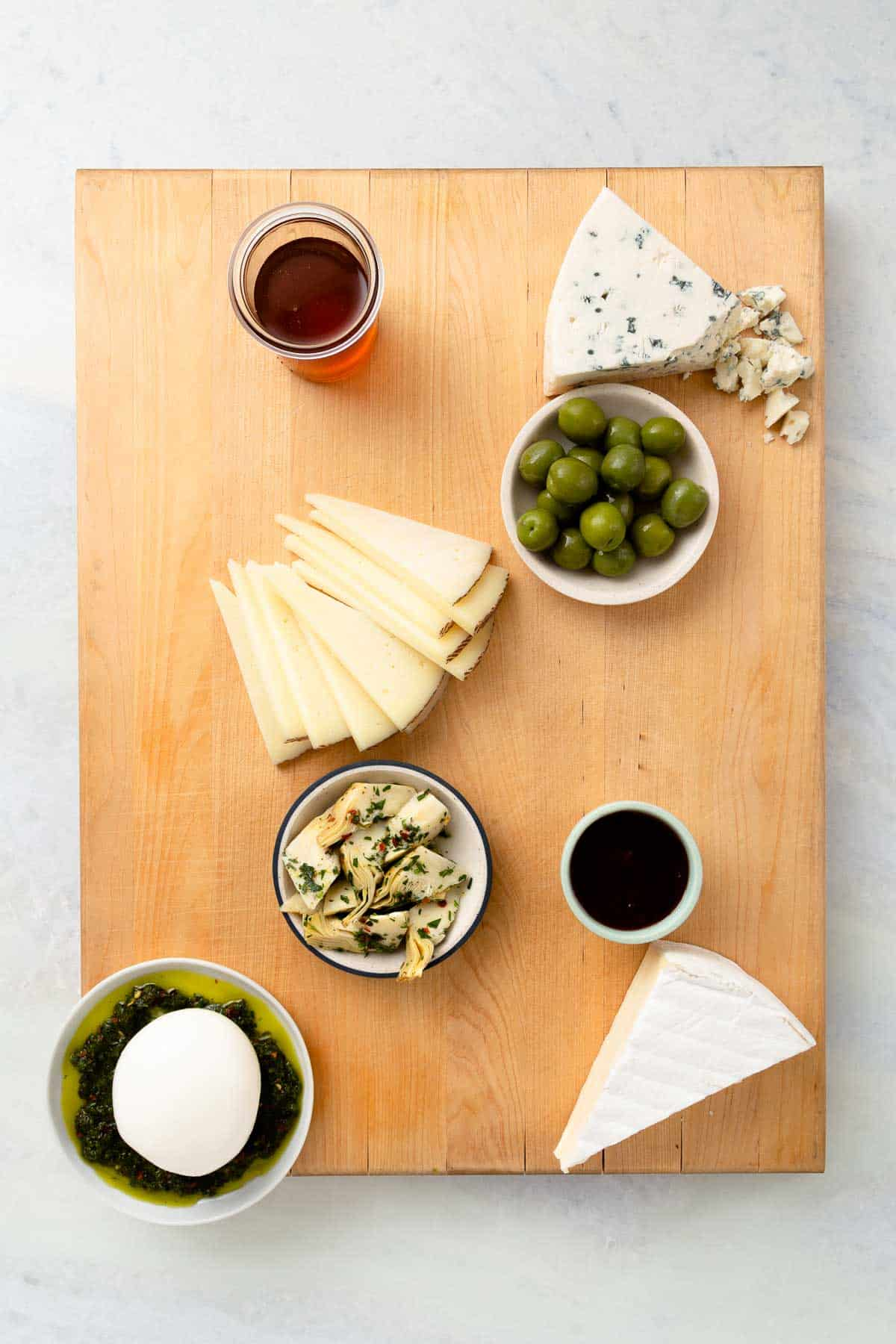 filling a large wood board with green olives, jam, and white cheeses