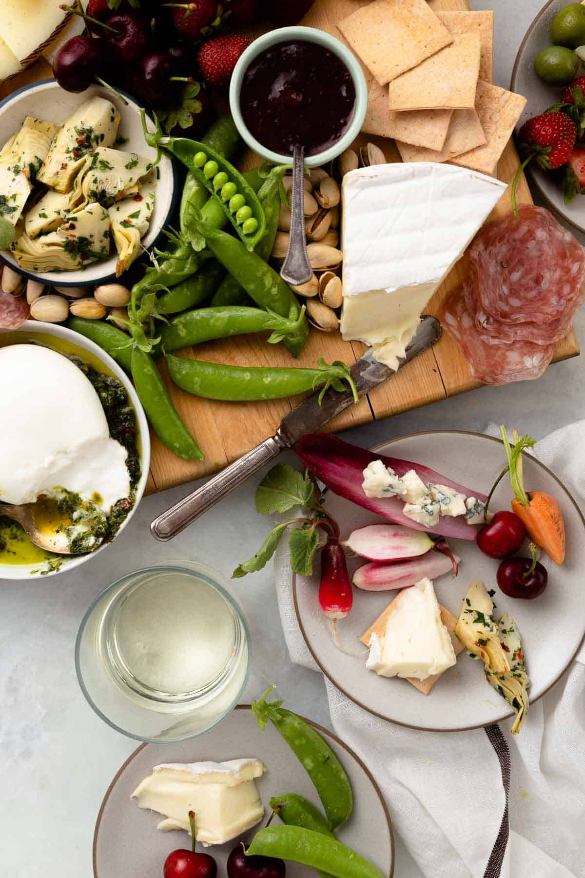 small white plates taking cheese and vegetables off of a large snack board